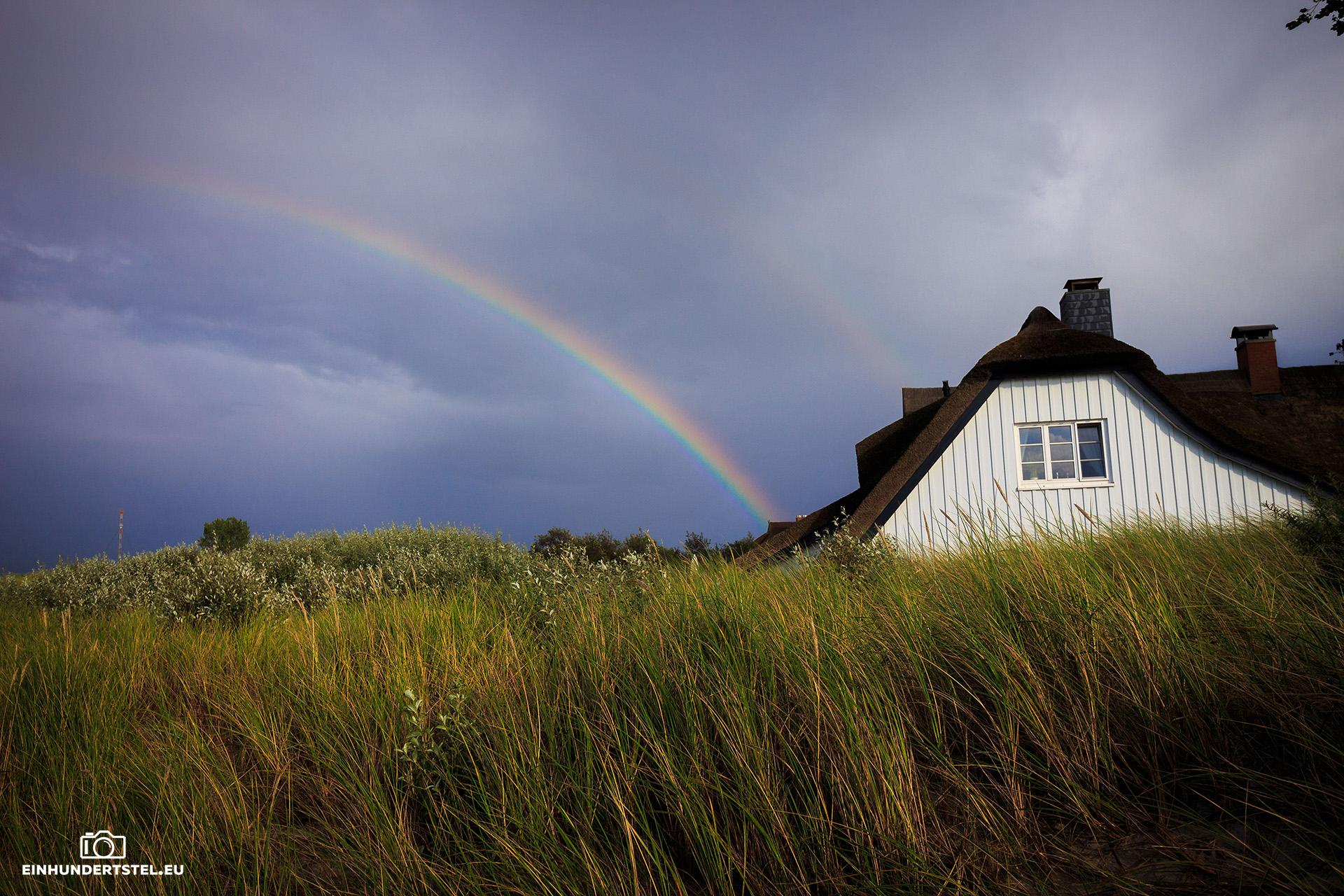 Regenbogen vor Haus mit Reetdach