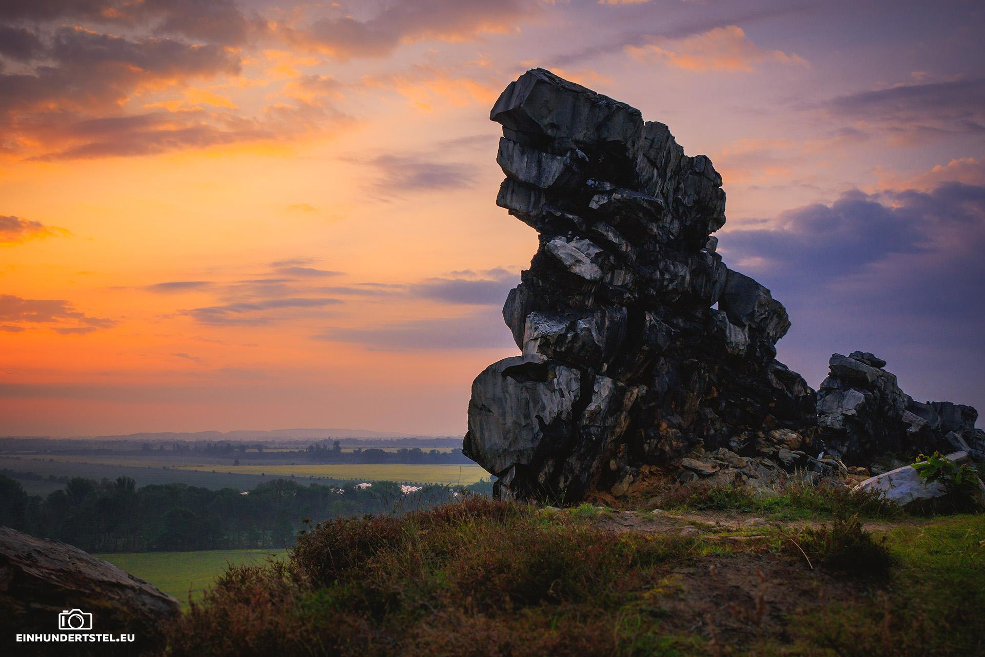 Hoher Felsen der Teufelsmauer. Links der Sonnenaufgang in kräftigem orange erahnbar. Im Vordergrund Wiese.