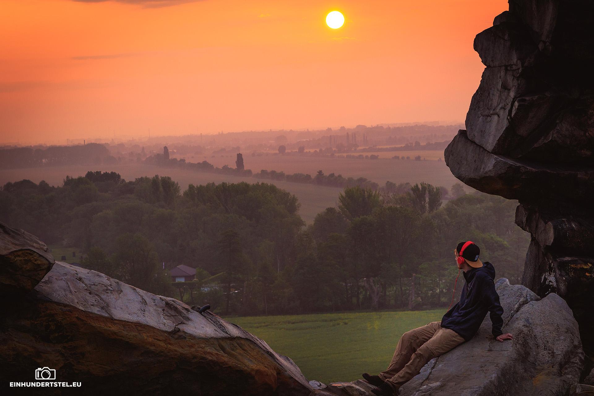 Rico mit roten Kopfhörern rechts auf einem Felsen der Teufelsmauer. Im Hintergrund eine Landschaft im morgendlichen Dunst. Sonnenaufgang in kräftigem Organge. Sonne am oberen Rand des Bildes zu sehn. Rico stützt sich nach hinten auf seine Hände und schaut entspannt in die Ferne.