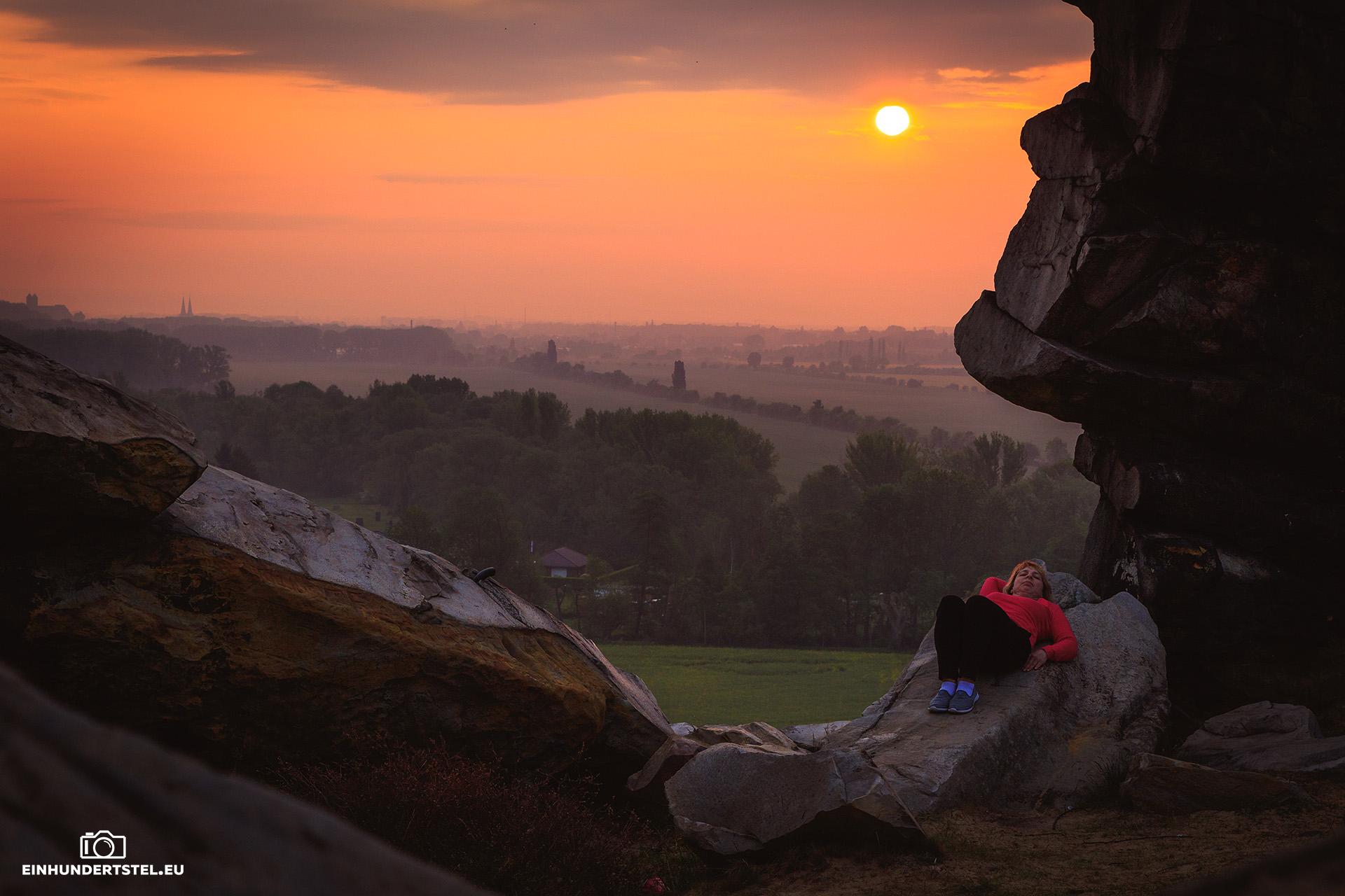 Sabine liegt auf einem Felsen der Teufelsmauer. Sonnenaufgang