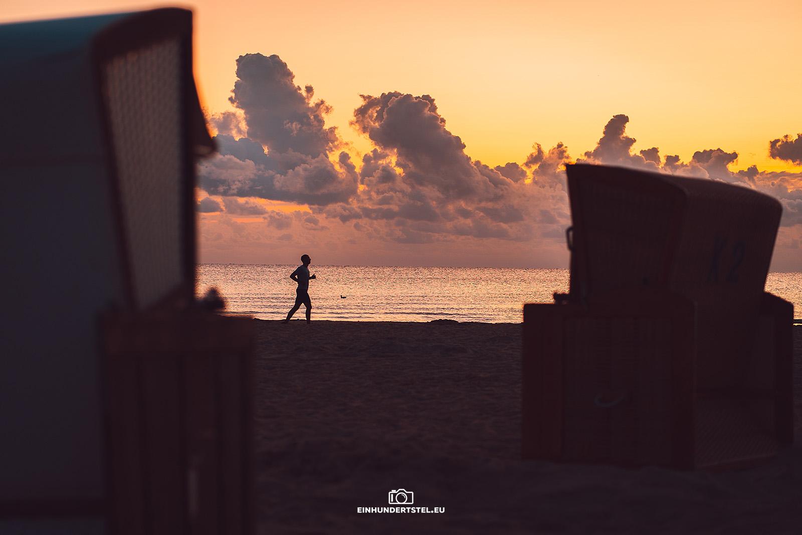 Jogger bei Sonnenaufgang am Strand von Karlshagen fotografiert durch zwei Strandkörbe. Im Hintergrund Wolken.