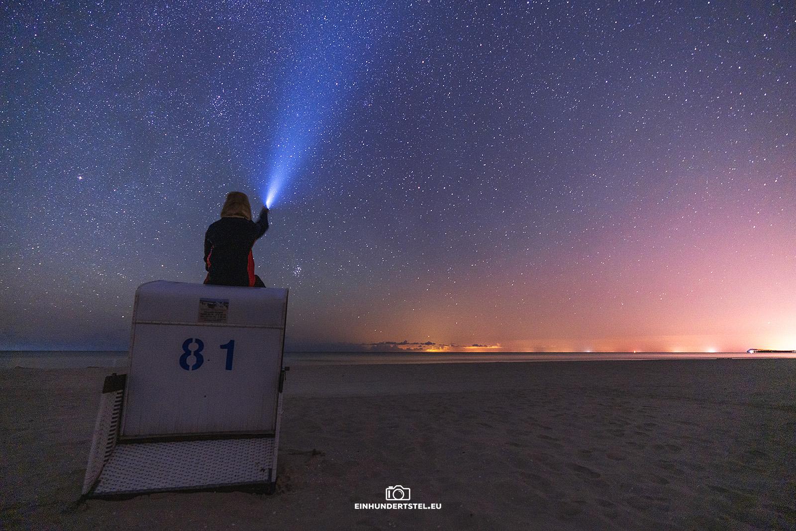 Person sitzt oben auf einem Strandkorb und leuchtet mit einer Taschenlampe in den Sternenhimmel am Strand von Karlshagen.