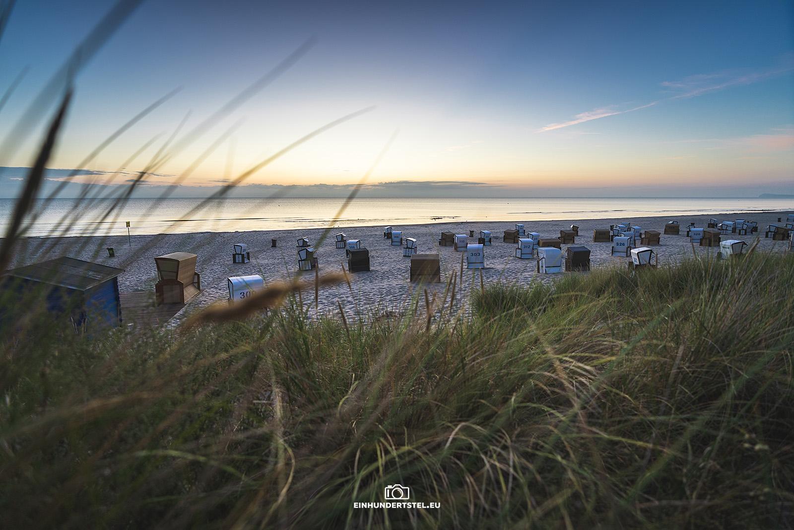 Strandkörbe hinter den Dünen bei Sonnenaufgang. Im Vordergrund leicht verschwommen Dünengras.
