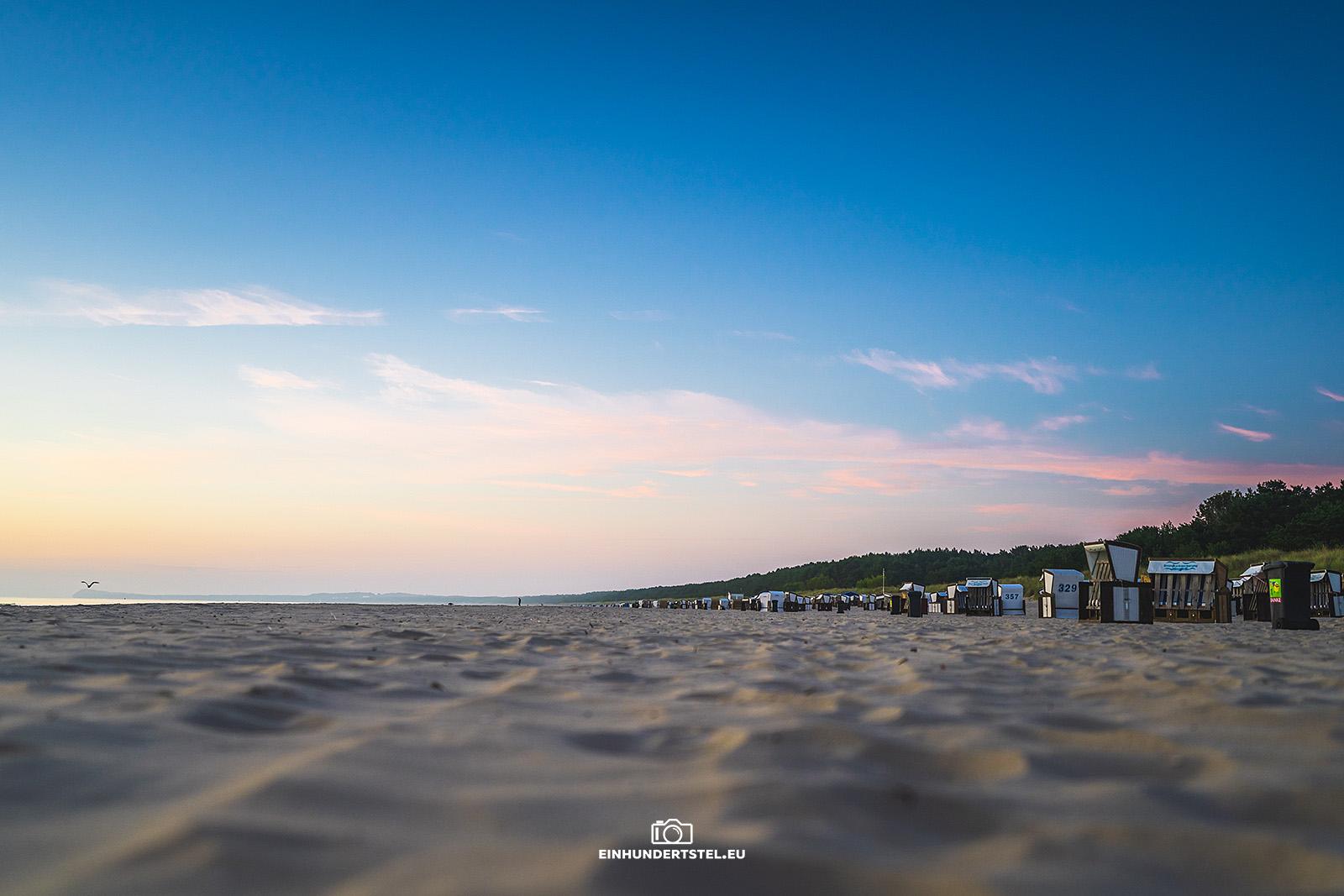 Sonnenaufgang am Strand von Karlshagen. Im Vordergrund Sand. Im Hintergrund Strandkörbe