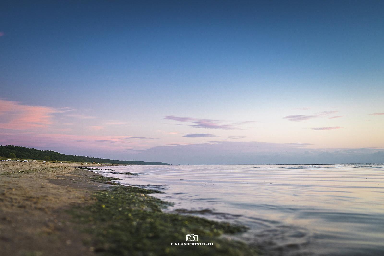 Sonnenaufgang am Strand von Karlsgagen. Rechts das Meer, links Strand. In der Mitte trennt ein Streifen von Seegras.