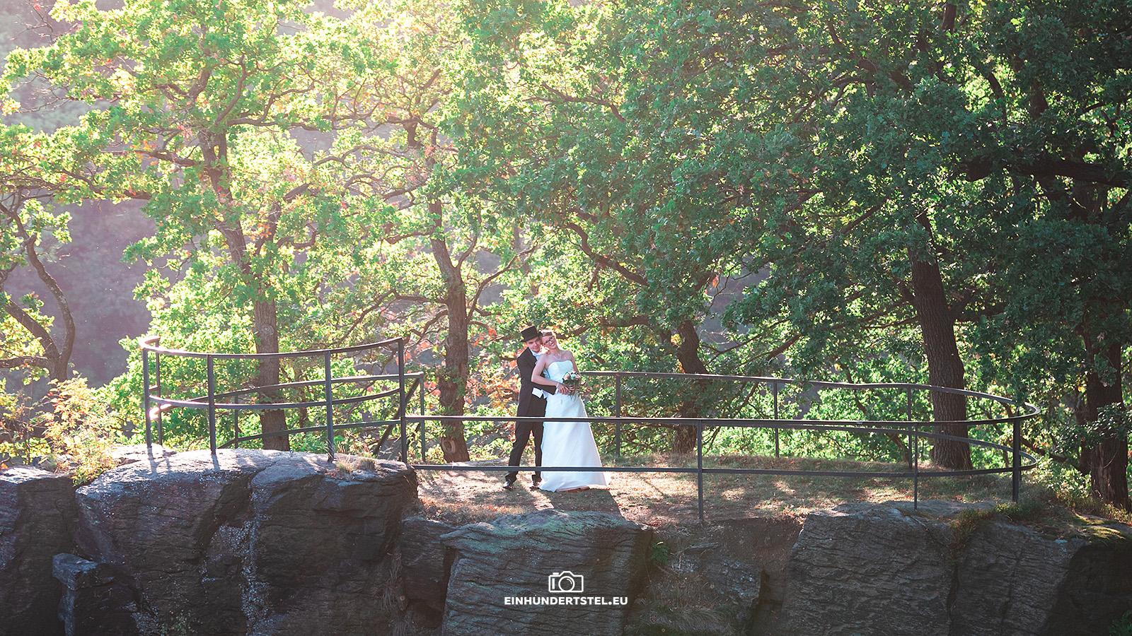 Brautpaar auf Felsen mit vielen Bäumen im Hintergrund bei Sonnenuntergang