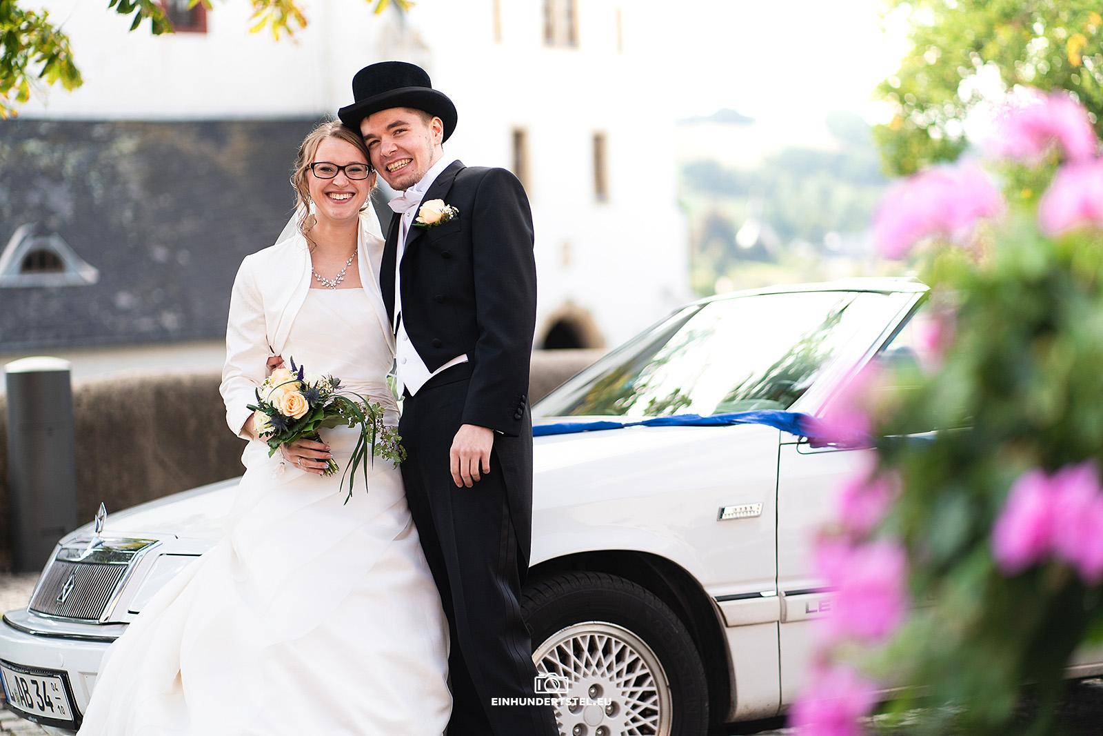 Brautpaar posiert vor Cabrio