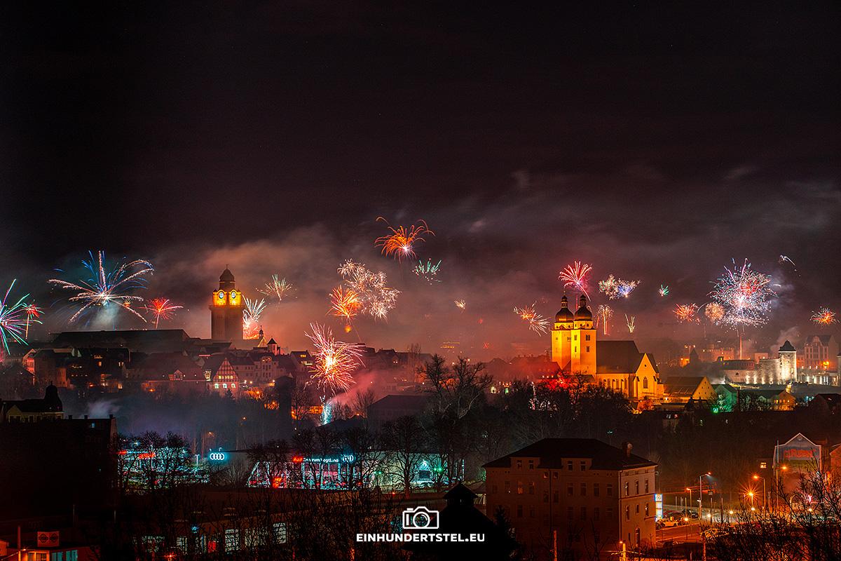 Sicht auf die Stadt Plauen im sächsischen Vogtland an Silvester. Zu sehen sind der Kirchturm und der Rathausturm. Überall steigen bunte Feuerwerksraketen in den Nachthimmel auf.