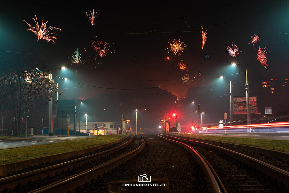 Bodennaher Blick über die Straßenbahnschienen in Richtung der neuen Elsterbrücke in Plauen. Am Nachthimmel explodieren gerade zahlreiche Silvesterraketen.