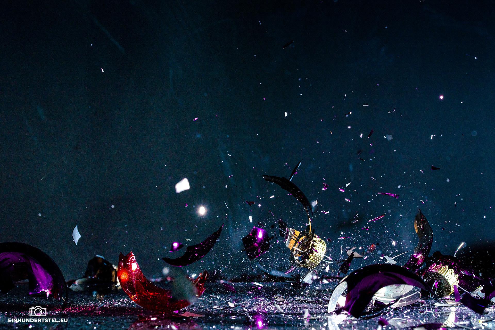 Mit Pulver gefüllte Weihnachtskugeln zerplatzen auf dem Boden. Splitter fliegen durch die Luft.
