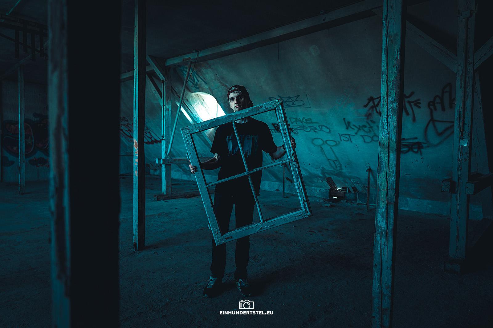 Eine Person steh in einem alten verlassen Haus und hält einen weißen Fensterrahmen in den Händen.