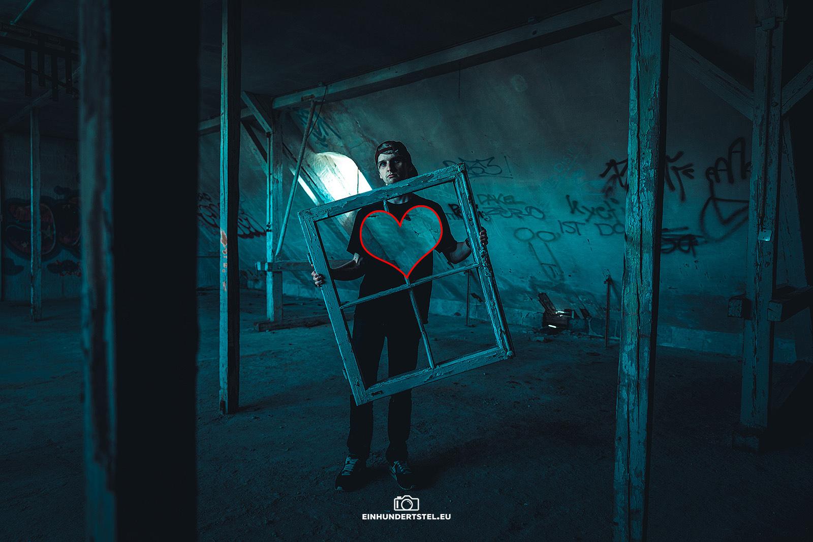 Eine Person steh in einem alten verlassen Haus und hält einen weißen Fensterrahmen in den Händen. Im Hintergrund scheint Licht durch ein Dachfenster.