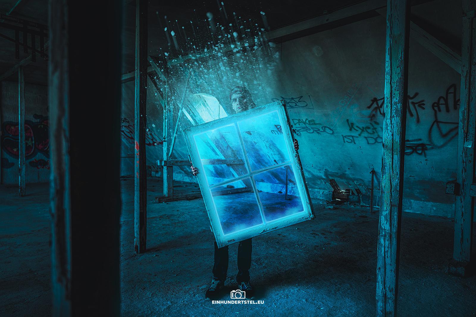 Eine Person steht in einem verlassenen Haus. Sie trägt einen Fensterrahmen, der ein magisches blaues Portal zu schein seint. Das Portal scheint die Person dahinter durchsichtig zu machen. Aus dem Portal strömen unzählige blaue Partikel heraus in die Luft.