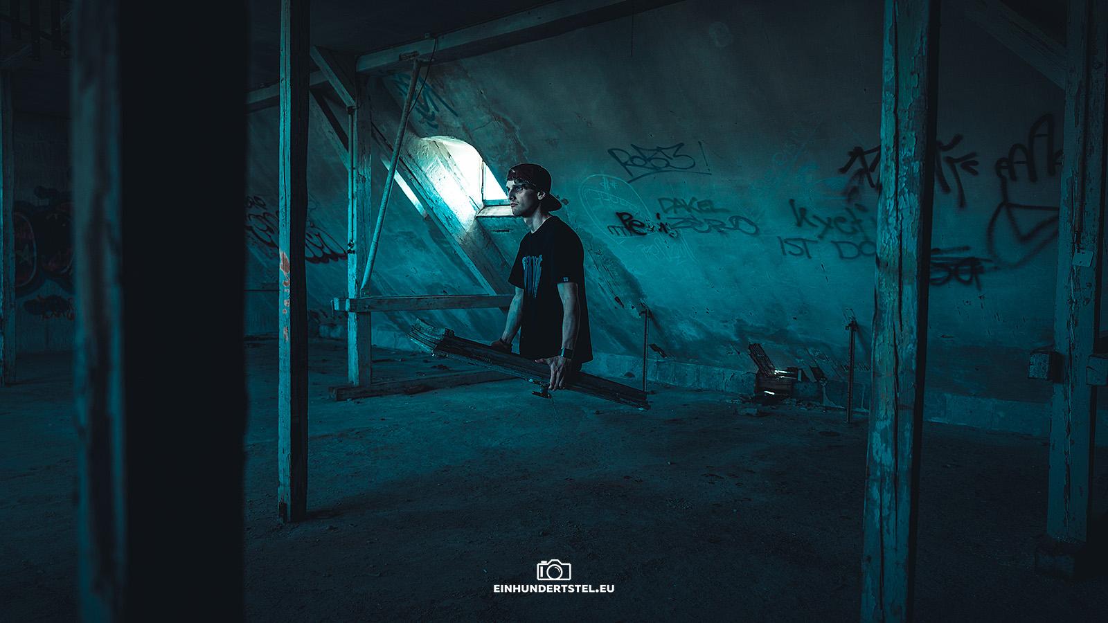 Ein Mann scheint aus einem Fensterrahmen zu steigen, den er selbst trägt. Er befindet sich in einem alten verlassenen Haus.